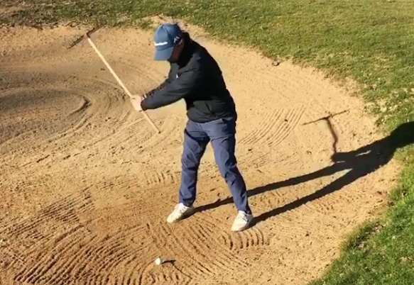 golfer uses bunker rake to hit shot out of sand