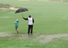 WATCH: Caddie protects young golfer from TORRENTIAL weather conditions